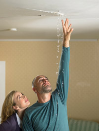 couple examining a leak in their ceiling
